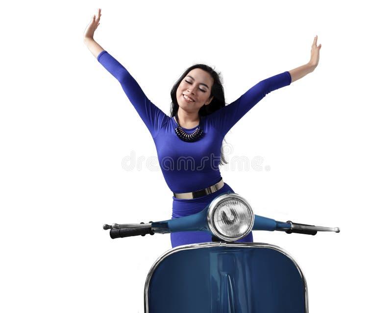 Η όμορφη ευτυχής ασιατική γυναίκα που οδηγά ένα μηχανικό δίκυκλο αυξάνει και τα δύο επάνω χέρια στοκ φωτογραφία με δικαίωμα ελεύθερης χρήσης