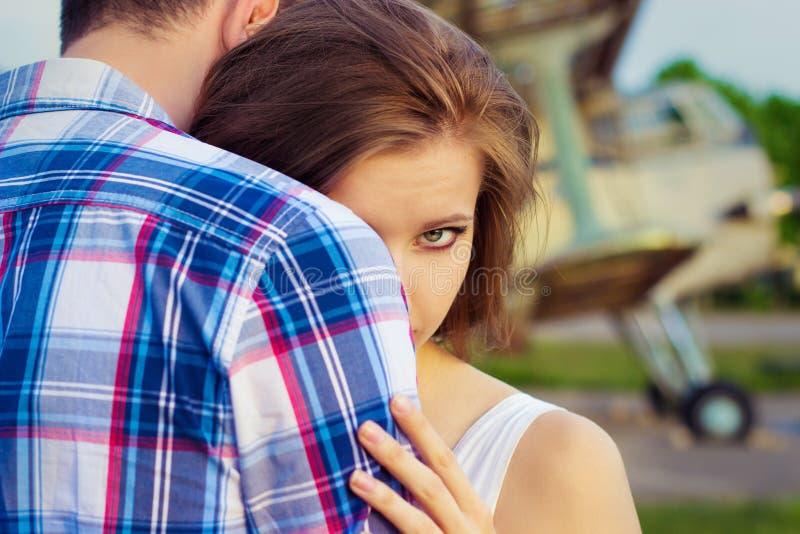Η όμορφη ευτυχής ερωτευμένη στάση ζευγών κοντά στα παλαιά αεροπλάνα που αγκαλιάζουν το κορίτσι κοιτάζει πέρα από τον ώμο του τύπο στοκ εικόνα