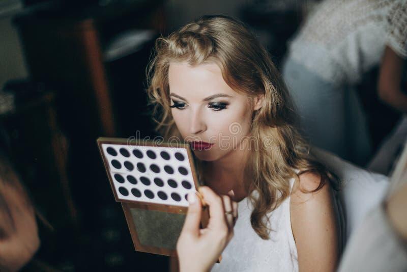 Η όμορφη ευτυχής νύφη που παίρνει το makeup της γίνοντα από τον επαγγελματία αποτελεί τον καλλιτέχνη και την εξέταση τον καθρέφτη στοκ εικόνα