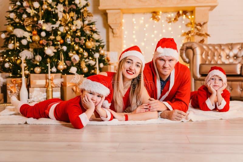 Η όμορφη ευτυχής οικογένεια στα κόκκινα φορέματα βρίσκεται κάτω από ένα χριστουγεννιάτικο δέντρο στοκ εικόνες με δικαίωμα ελεύθερης χρήσης