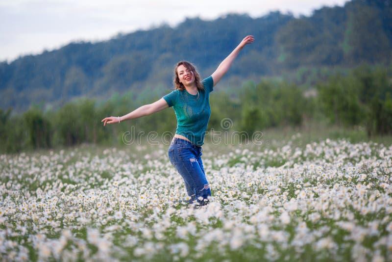 Η όμορφη ευτυχής χαμογελώντας γυναίκα στο camomile τομέα περπατά κάτω από τη βροχή, χρόνος άνοιξη στοκ φωτογραφία