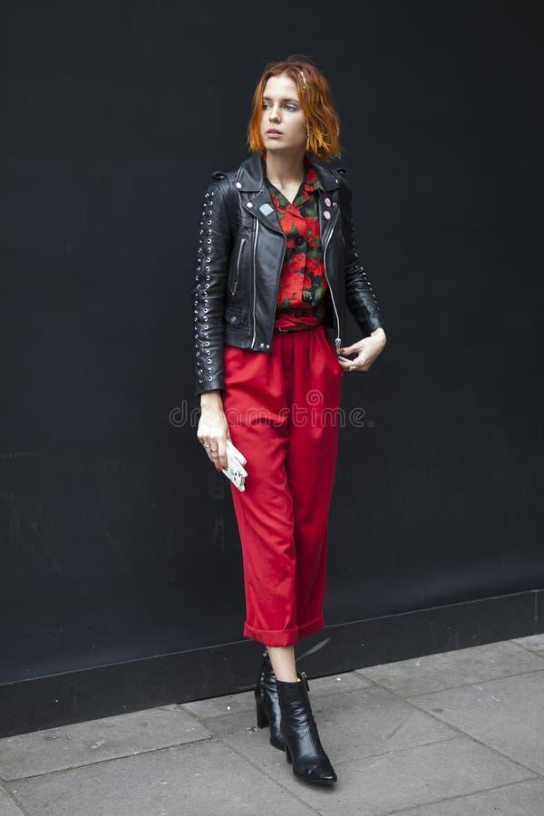 Η όμορφη και μοντέρνη γυναίκα στο κόκκινο παντελόνι και το μαύρο leasher ντύνουν την τοποθέτηση κατά τη διάρκεια της εβδομάδας μό στοκ εικόνες