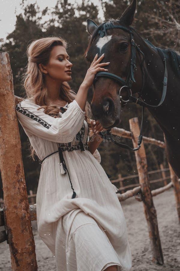 Η όμορφη και τρυφερή νέα γυναίκα που φορά το φόρεμα αγκαλιάζει και κτυπά το άλογο στο αγρόκτημα στοκ εικόνα με δικαίωμα ελεύθερης χρήσης
