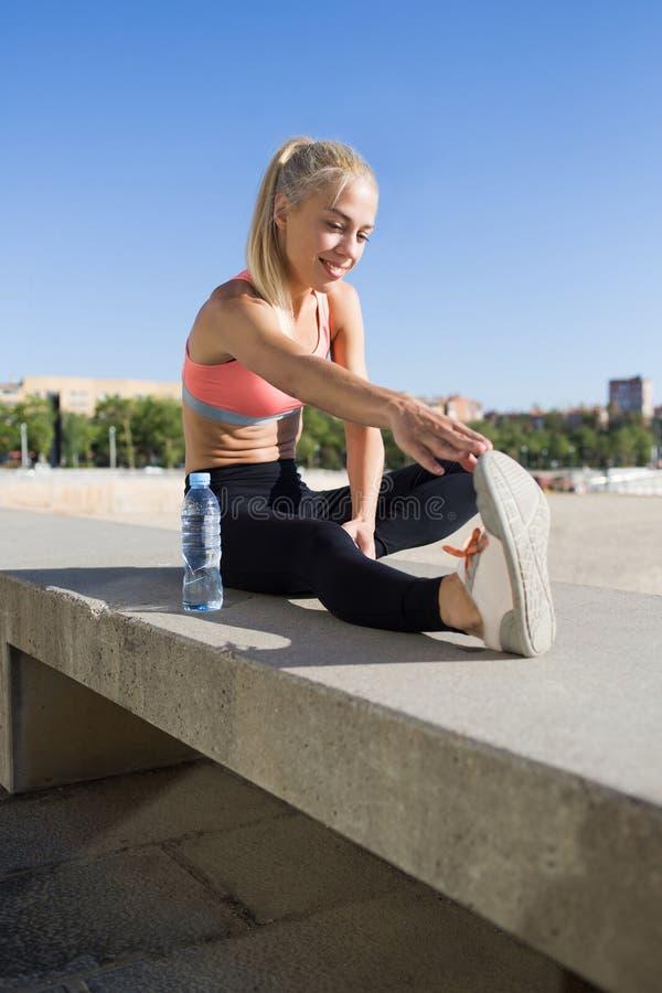 Η όμορφη κατάλληλη γυναίκα έντυσε στον αθλητικό στηθόδεσμο που κάνει τις ασκήσεις προθέρμανσης στο καθαρό αέρα στοκ εικόνες