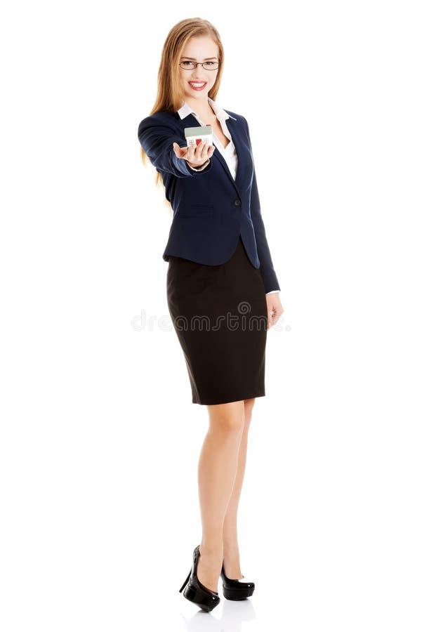 Η όμορφη καυκάσια επιχειρησιακή γυναίκα κρατά το πρότυπο σπιτιών στοκ εικόνες