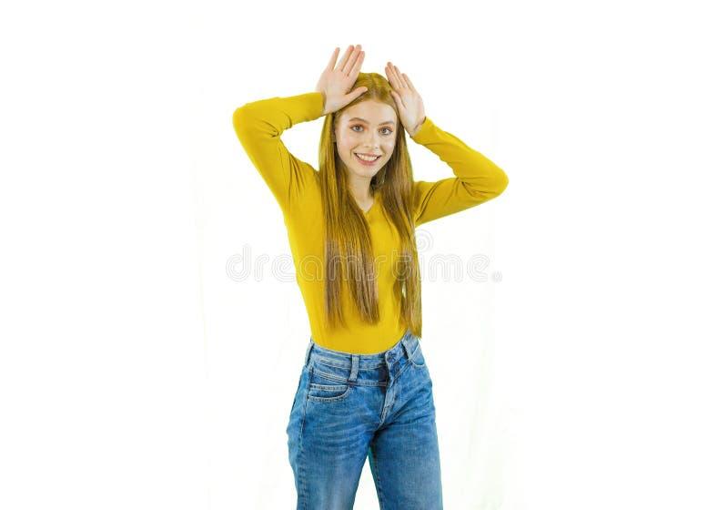Η όμορφη κοκκινομάλλης γυναίκα χαμογελά παιχνιδιάρικα και μιμείται τα αυτιά της με τα χέρια της στο κεφάλι της ενάντια απομονωμέν στοκ φωτογραφία με δικαίωμα ελεύθερης χρήσης