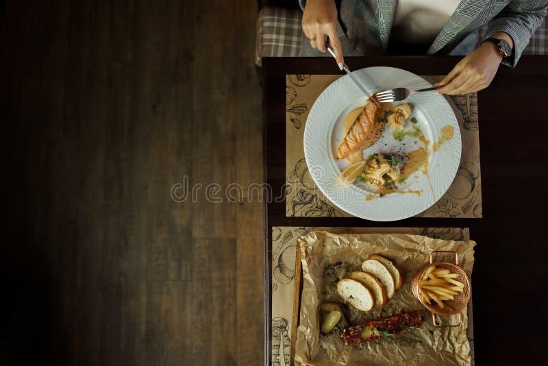 Η όμορφη κυρία κάθεται σε έναν πίνακα σε ένα εστιατόριο και τρώει την ψημένη λωρίδα σολομών με τους σπόρους και το κουνουπίδι κολ στοκ φωτογραφίες