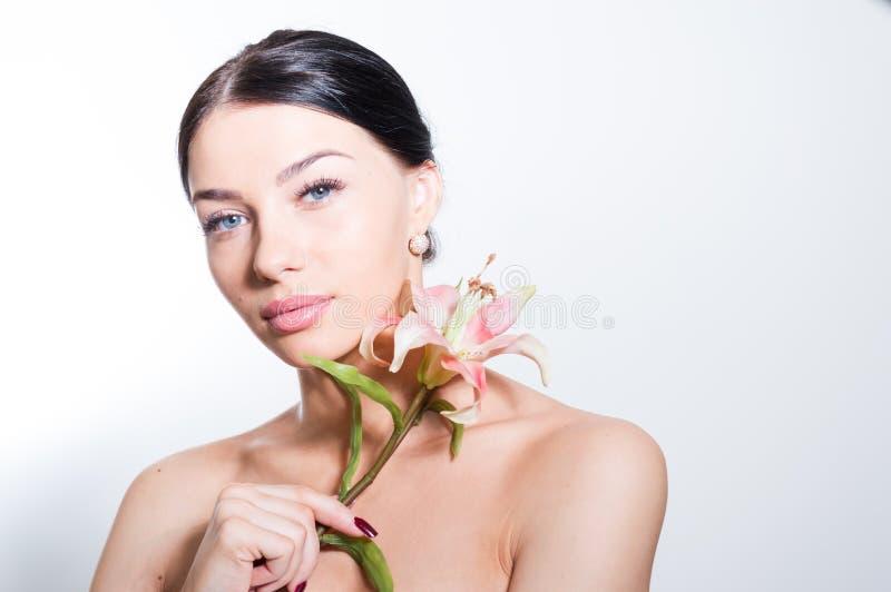 Η όμορφη κυρία με ανθίζει lilly τέλειο δέρμα στοκ φωτογραφία