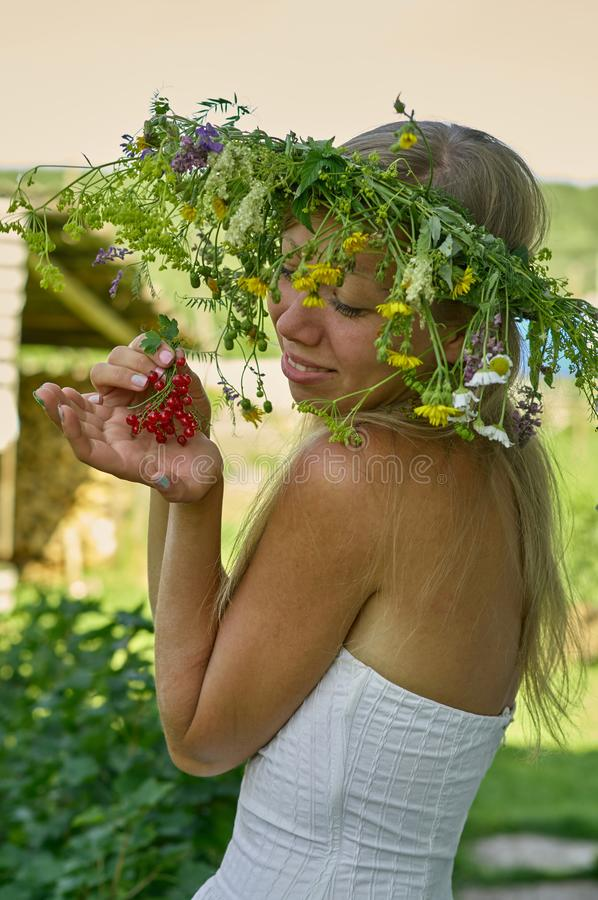 Η όμορφη μακρύς-άσπρη γυναίκα τρίχας στο άσπρο στεφάνι φορεμάτων και λουλουδιών κρατά τη διαθέσιμη δέσμη χεριών των μούρων κόκκιν στοκ φωτογραφίες με δικαίωμα ελεύθερης χρήσης