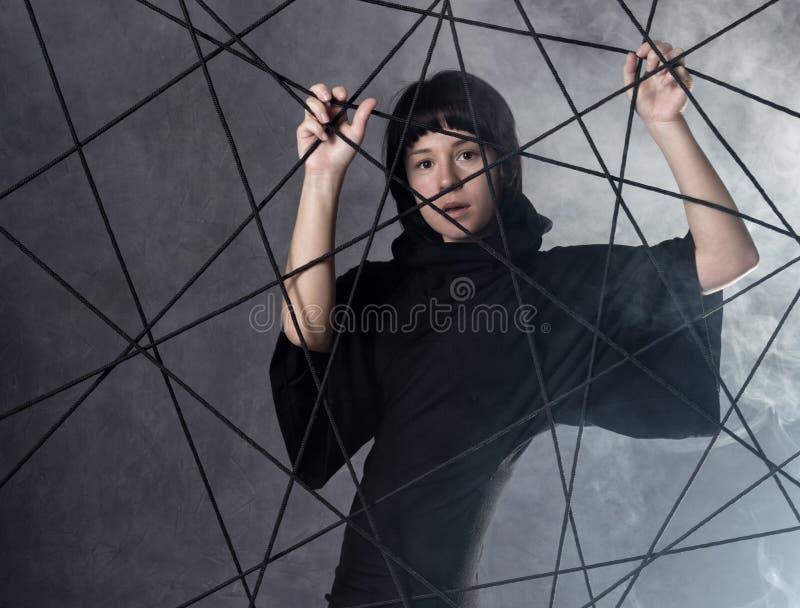 Η όμορφη μοντέρνη κυρία που φορά ένα γοτθικό μαύρο φόρεμα με το υψηλό περιλαίμιο, θέτει στον άσπρο καπνό σε ένα γκρίζο υπόβαθρο στοκ φωτογραφία με δικαίωμα ελεύθερης χρήσης