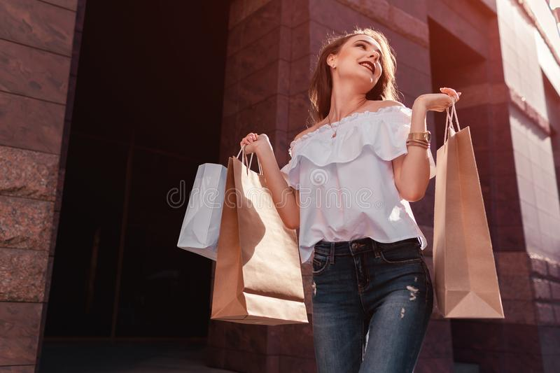 Η όμορφη μοντέρνη νέα γυναίκα με τις αγορές τοποθετεί το περπάτημα στην οδό πόλεων το καλοκαίρι σε σάκκο Ευτυχής και συγκινημένος στοκ φωτογραφία με δικαίωμα ελεύθερης χρήσης