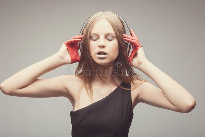 Η όμορφη μουσική ακούσματος κοριτσιών μόδας με τα ακουστικά, που φορούν τα κόκκινα γάντια, ιδιαίτερες προσοχές και παίρνει την ευ στοκ εικόνα