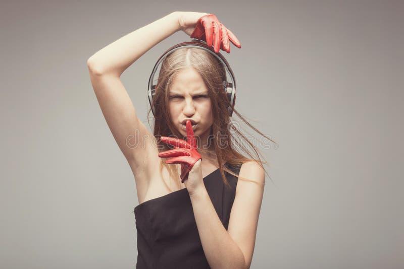 Η όμορφη μουσική ακούσματος κοριτσιών μόδας με τα ακουστικά, που φορούν τα κόκκινα γάντια, παίρνει την ευχαρίστηση με το τραγούδι στοκ εικόνα με δικαίωμα ελεύθερης χρήσης