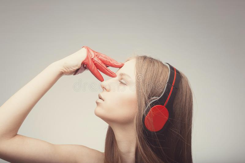 Η όμορφη μουσική ακούσματος κοριτσιών μόδας με τα ακουστικά, που φορούν τα κόκκινα γάντια, ιδιαίτερες προσοχές και παίρνει την ευ στοκ εικόνες