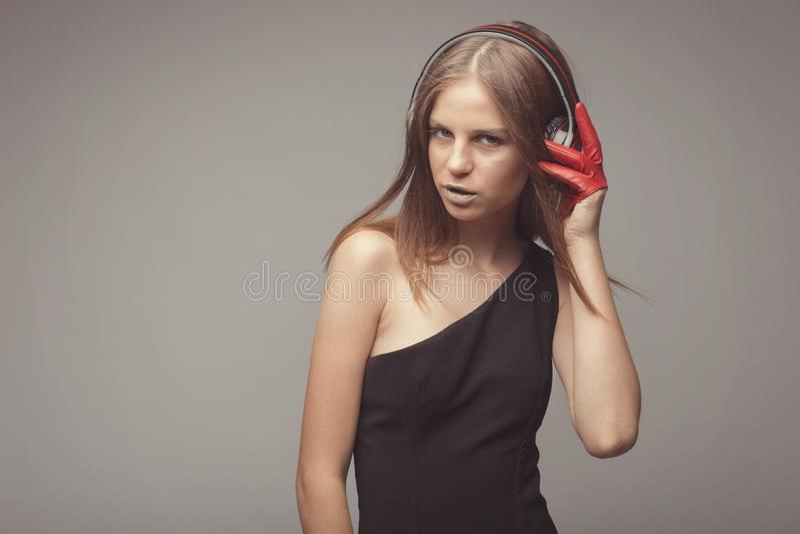 Η όμορφη μουσική ακούσματος κοριτσιών μόδας με τα ακουστικά, που φορούν τα κόκκινα γάντια, παίρνει την ευχαρίστηση με το τραγούδι στοκ εικόνες