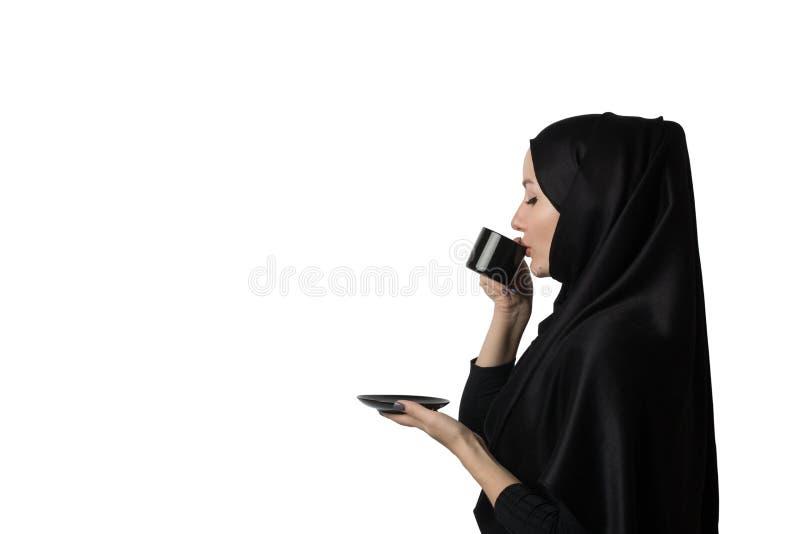 Η όμορφη μουσουλμανική γυναίκα στο μαύρο hijab πίνει τον καφέ ή το τσάι με την ευχαρίστηση στοκ εικόνα με δικαίωμα ελεύθερης χρήσης