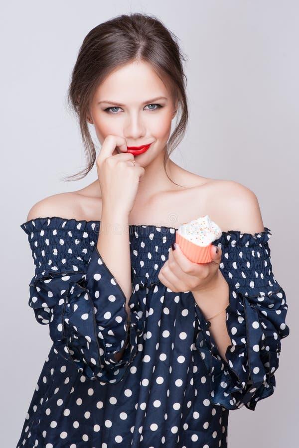 Η όμορφη νέα αναδρομική γυναίκα pinup τρώει τα γλυκά τρόφιμα κέικ που απομονώνονται στο άσπρο στούντιο iin στοκ εικόνα