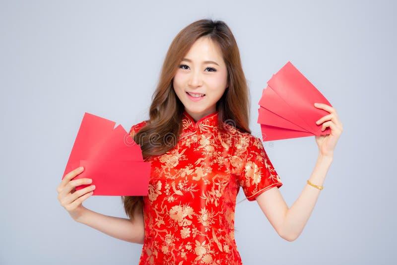 Η όμορφη νέα ασιατική γυναίκα πορτρέτου cheongsam ντύνει τον κόκκινο φάκελο εκμετάλλευσης χαμόγελου στο άσπρο υπόβαθρο στοκ εικόνες