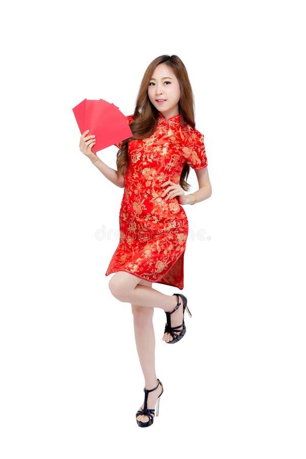Η όμορφη νέα ασιατική γυναίκα πορτρέτου cheongsam ντύνει τον κόκκινο φάκελο εκμετάλλευσης χαμόγελου στο άσπρο υπόβαθρο στοκ φωτογραφία