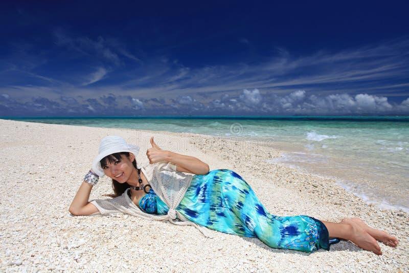 Η όμορφη νέα γυναίκα βρίσκεται στην παραλία στοκ εικόνα