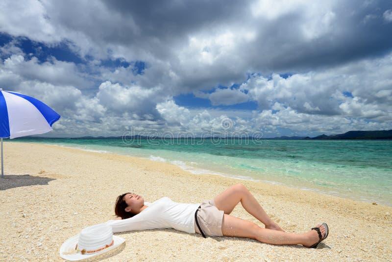 Η όμορφη νέα γυναίκα βρίσκεται στην παραλία στοκ εικόνες με δικαίωμα ελεύθερης χρήσης