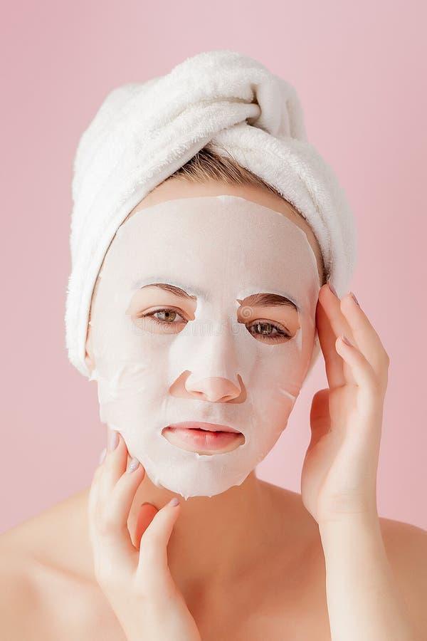 Η όμορφη νέα γυναίκα εφαρμόζει μια καλλυντική μάσκα ιστού σε ένα πρόσωπο σε ένα ρόδινο υπόβαθρο Επεξεργασία υγειονομικής περίθαλψ στοκ φωτογραφία με δικαίωμα ελεύθερης χρήσης