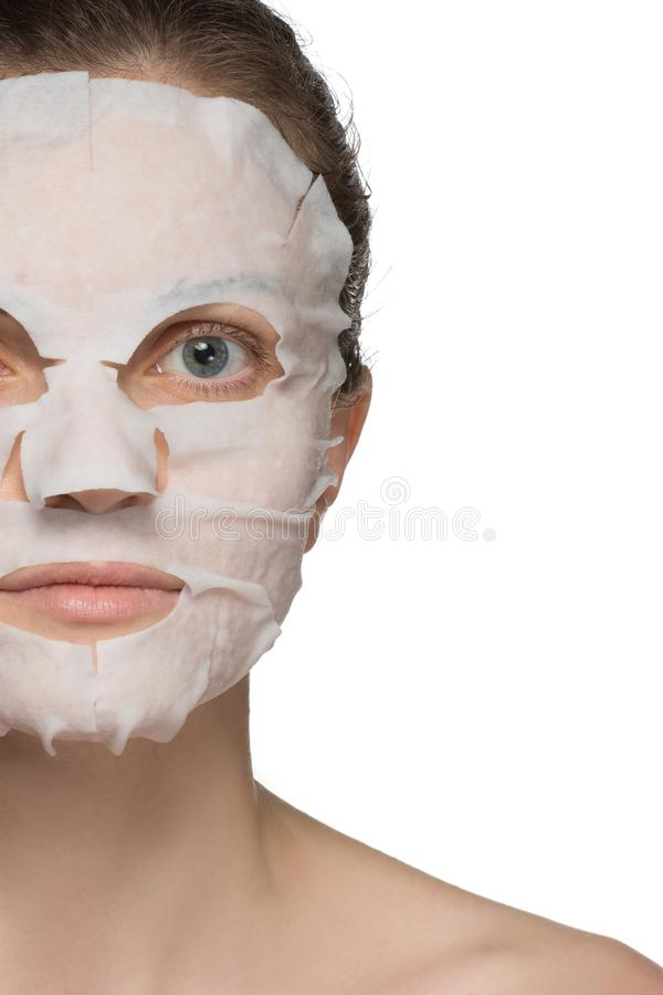 Η όμορφη νέα γυναίκα εφαρμόζει μια καλλυντική μάσκα σε ένα πρόσωπο στο α στοκ φωτογραφία με δικαίωμα ελεύθερης χρήσης