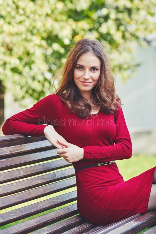 Η όμορφη νέα γυναίκα κάθεται σε έναν πάγκο στοκ φωτογραφία με δικαίωμα ελεύθερης χρήσης
