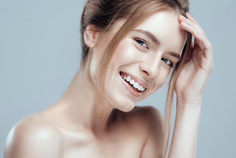 Η όμορφη νέα γυναίκα κινηματογραφήσεων σε πρώτο πλάνο με το καθαρό φρέσκο δέρμα αγγίζει το πρόσωπό της Φυσική ομορφιά και SPA στοκ εικόνες