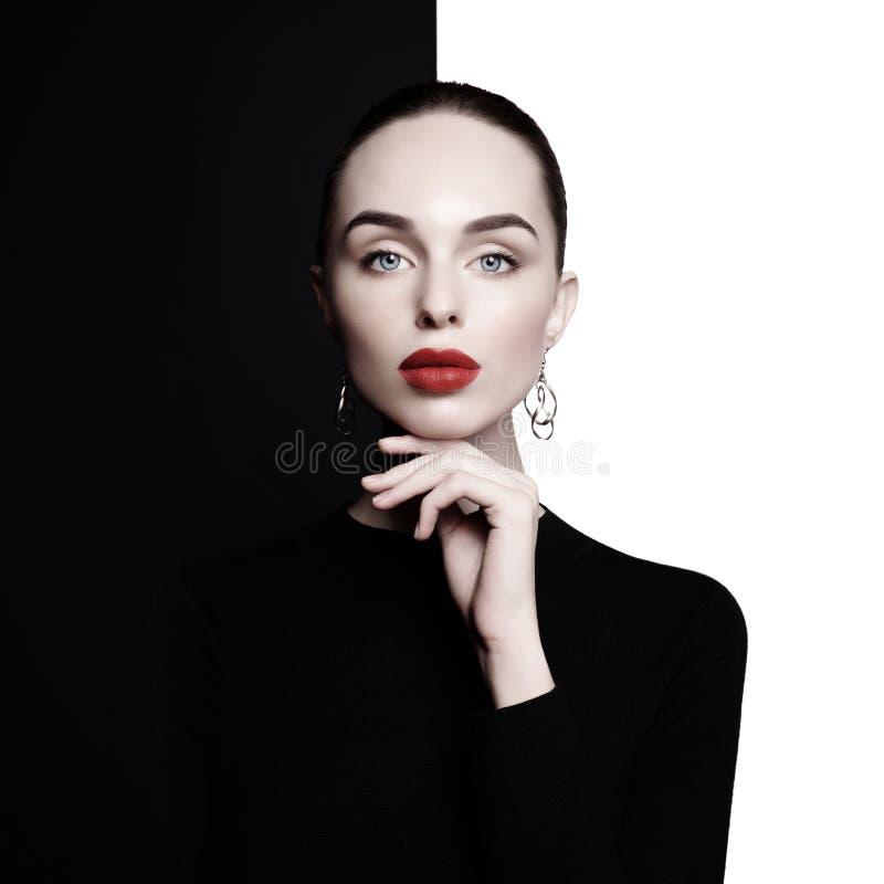 Η όμορφη νέα γυναίκα με τα μεγάλα σκουλαρίκια θέτει στο στούντιο στοκ φωτογραφία με δικαίωμα ελεύθερης χρήσης
