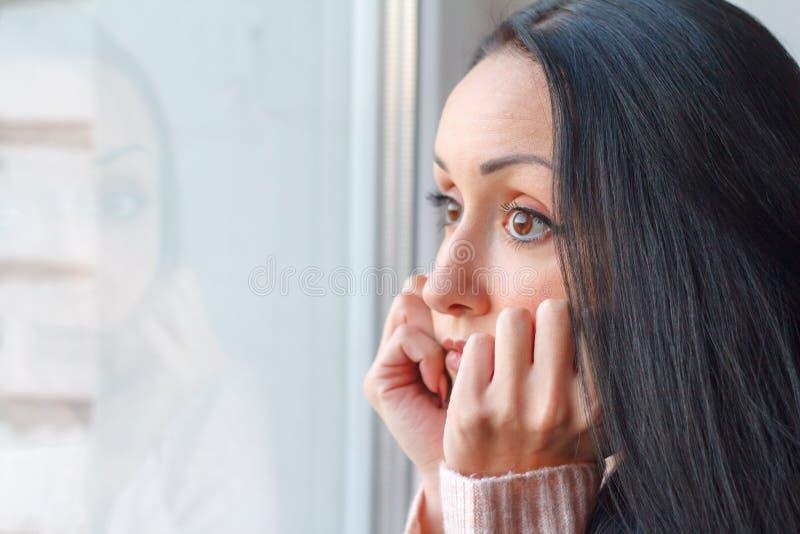 Η όμορφη νέα γυναίκα με τη μακριά μαύρη τρίχα είναι λυπημένη από το παράθυρο, το υπόβαθρο ή την έννοια της μοναξιάς και της προσδ στοκ φωτογραφίες με δικαίωμα ελεύθερης χρήσης