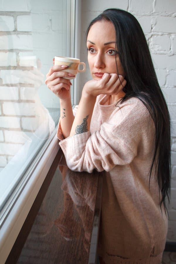 Η όμορφη νέα γυναίκα με τη μακριά μαύρη τρίχα πίνει τον καφέ, φαίνεται έξω το παράθυρο, που απεικονίζεται στο παράθυρο και window στοκ εικόνες