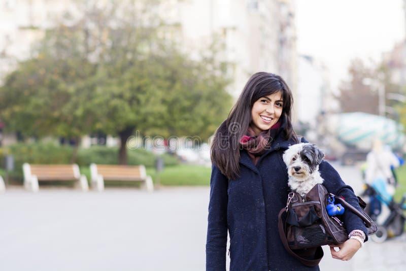 Η όμορφη νέα γυναίκα με το άσπρο σκυλί φέρνει μέσα την τσάντα στοκ φωτογραφίες
