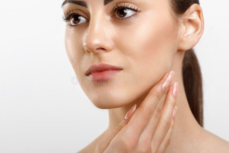 Η όμορφη νέα γυναίκα με το καθαρό φρέσκο δέρμα που εφαρμόζει την κρέμα και αγγίζει το πρόσωπο o cosmetology E στοκ εικόνα