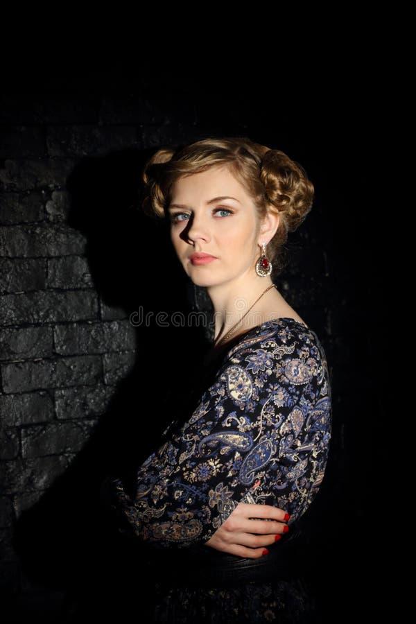 Η όμορφη νέα γυναίκα με το hairdo και makeup θέτει στο σκοτάδι στοκ εικόνες