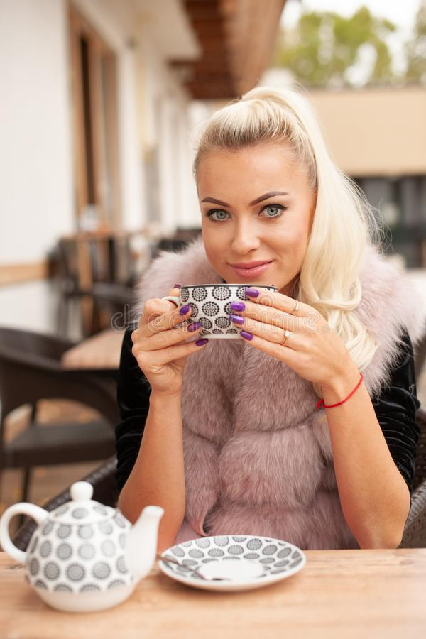 Η όμορφη νέα γυναίκα πίνει το τσάι στο φραγμό terace το πρώιμο φθινόπωρο στοκ φωτογραφία