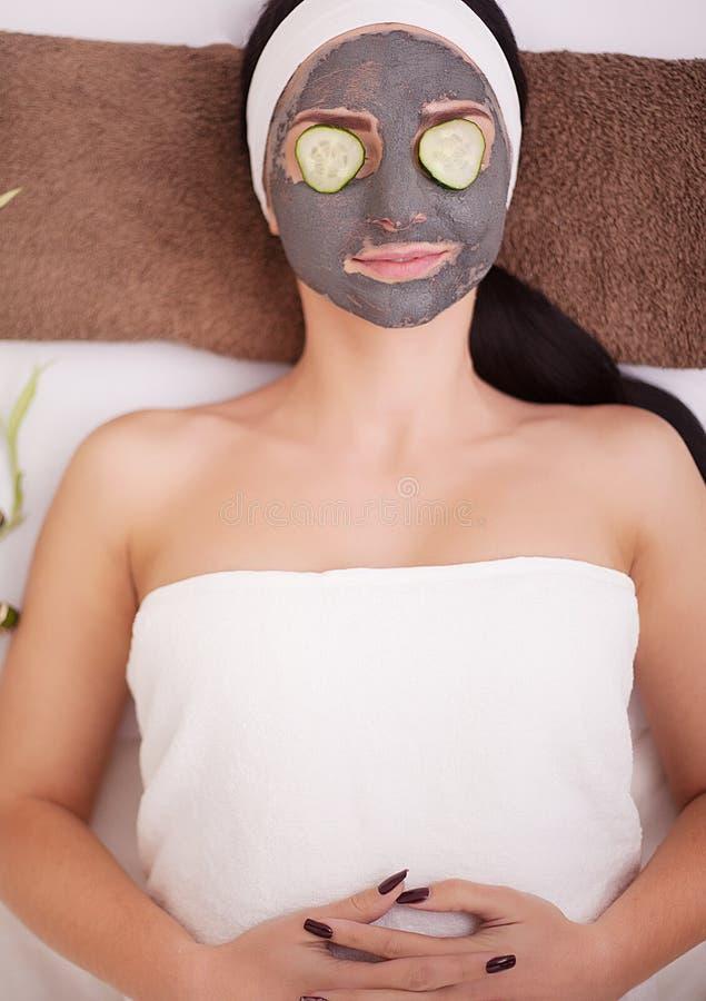 Η όμορφη νέα γυναίκα παίρνει την του προσώπου μάσκα αργίλου στη SPA, που εναπόκειται στα αγγούρια στα μάτια στοκ εικόνα