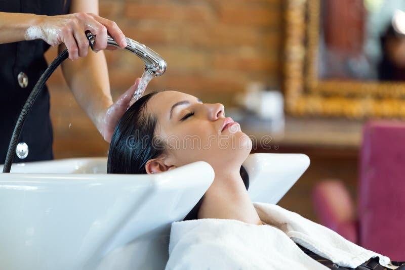 Η όμορφη νέα γυναίκα πλένει την τρίχα σε ένα σαλόνι ομορφιάς στοκ φωτογραφίες με δικαίωμα ελεύθερης χρήσης
