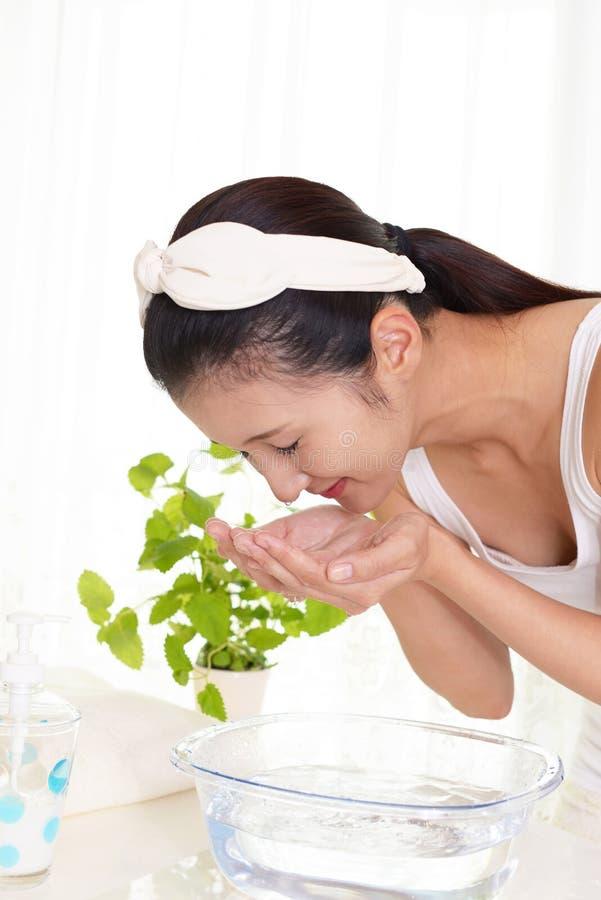 Γυναίκα που πλένει το πρόσωπό της στοκ εικόνα