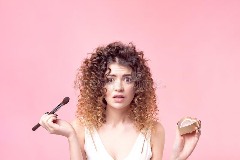 Η όμορφη νέα γυναίκα που εφαρμόζει τη σκόνη ιδρύματος ή κοκκινίζει με τη βούρτσα makeup στοκ φωτογραφίες με δικαίωμα ελεύθερης χρήσης