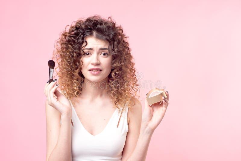 Η όμορφη νέα γυναίκα που εφαρμόζει τη σκόνη ιδρύματος ή κοκκινίζει με τη βούρτσα makeup στοκ εικόνες