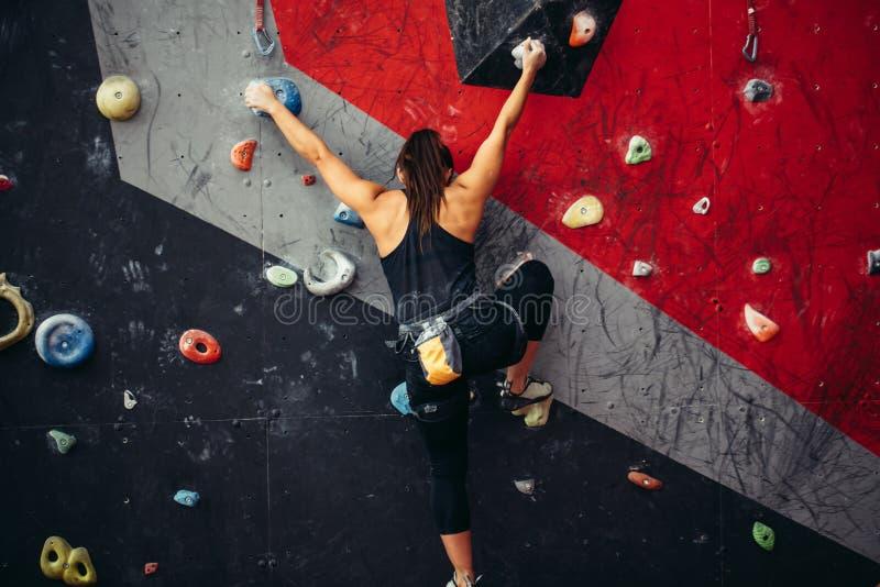Η όμορφη νέα γυναίκα που παίρνει έναν μεγάλο επιταχύνει έναν τεχνητό τοίχο στοκ φωτογραφίες