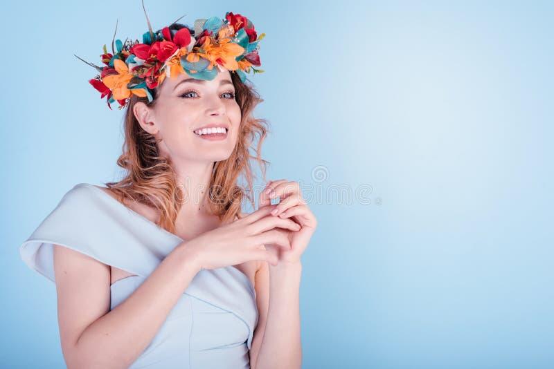Η όμορφη νέα γυναίκα που φορά τη floral headband κορώνα τιαρών απομόνωσε το ανοικτό μπλε υπόβαθρο, χαμόγελο στοκ φωτογραφίες
