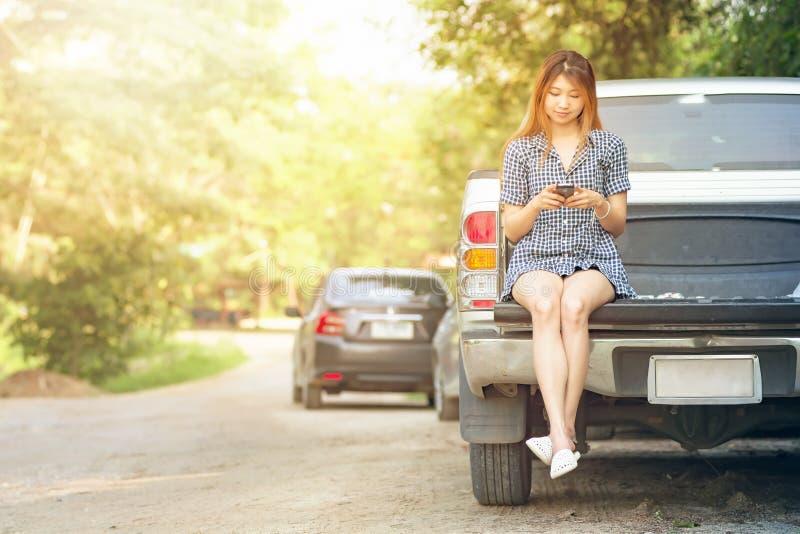 Η όμορφη νέα γυναίκα που χρησιμοποιεί το κινητό τηλέφωνό της κάθεται στο αυτοκίνητο στοκ εικόνες