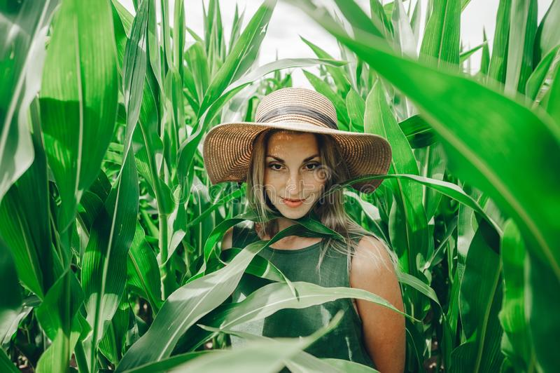 Η όμορφη νέα γυναίκα στο καπέλο αχύρου είναι σε έναν τομέα καλαμποκιού στοκ εικόνες