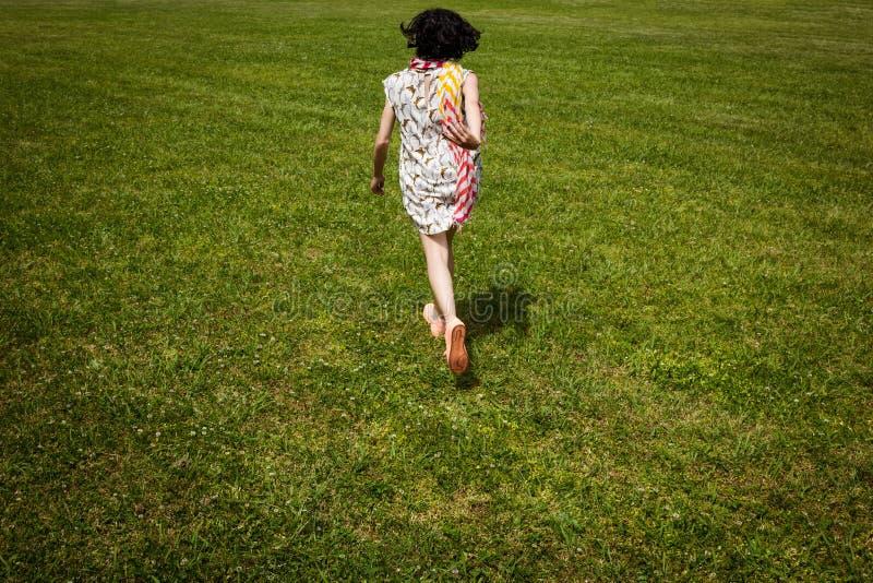 Η όμορφη νέα γυναίκα τρέχει μακριά στον πράσινο τομέα χλόης στοκ εικόνες