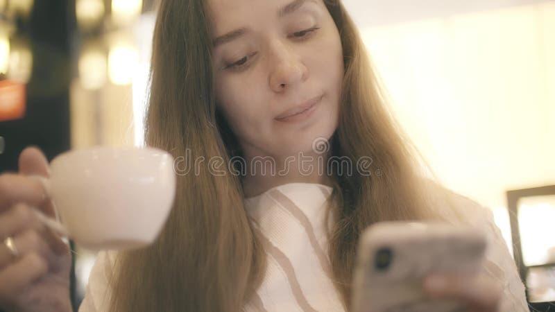 Η όμορφη νέα γυναίκα χρησιμοποιεί το smartphone της ενώ έχοντας το τσάι ή τον καφέ σε έναν καφέ στοκ εικόνα