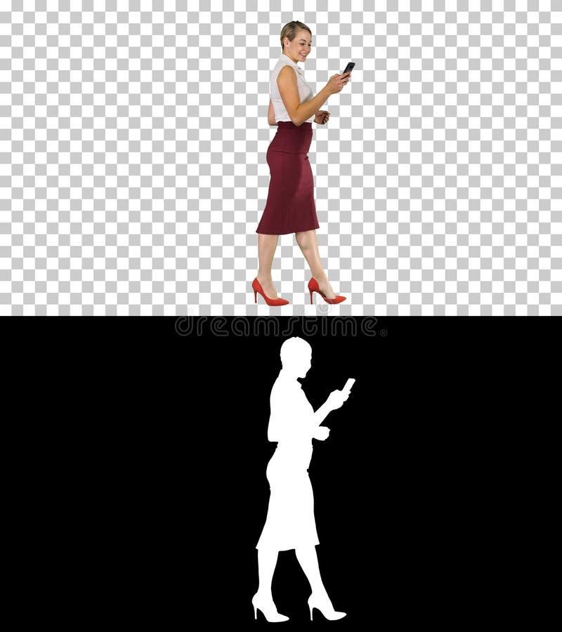 Η όμορφη νέα γυναίκα χρησιμοποιεί app στη συσκευή smartphone της για να στείλει ένα μήνυμα κειμένου και περπατά, άλφα κανάλι στοκ φωτογραφία με δικαίωμα ελεύθερης χρήσης