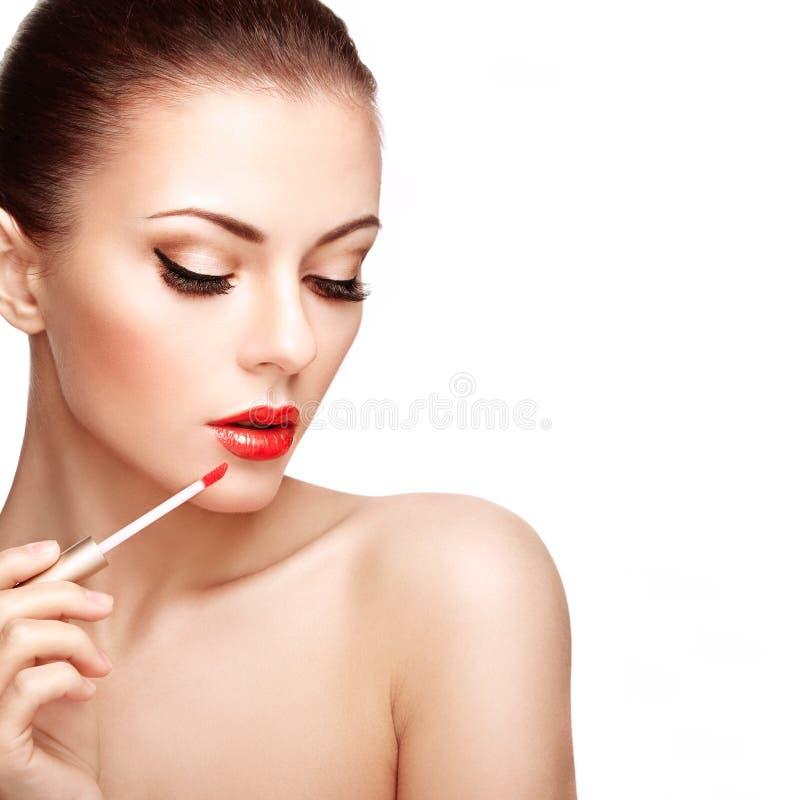 Η όμορφη νέα γυναίκα χρωματίζει τα χείλια με το κραγιόν στοκ φωτογραφίες