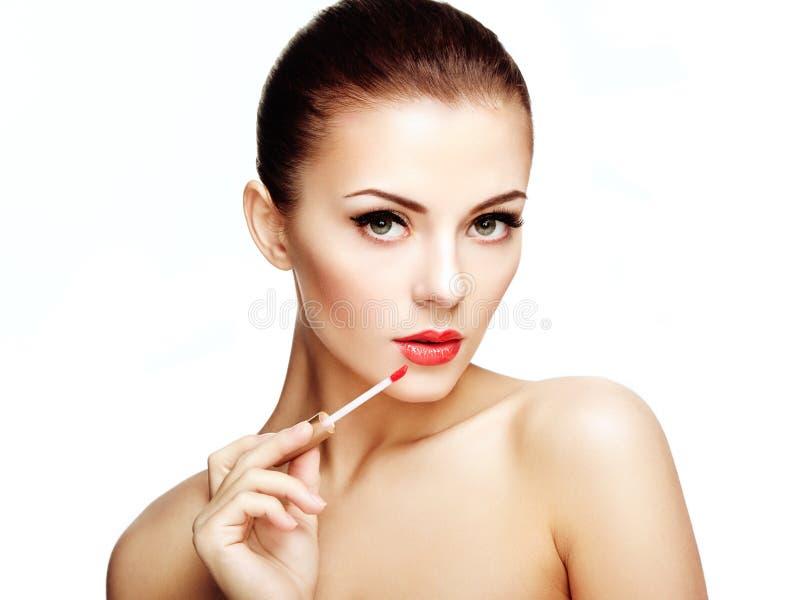 Η όμορφη νέα γυναίκα χρωματίζει τα χείλια με το κραγιόν. Τέλεια σύνθεση στοκ φωτογραφίες με δικαίωμα ελεύθερης χρήσης